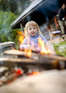 Excited cute little girl outside the cottage is looking at camfire.