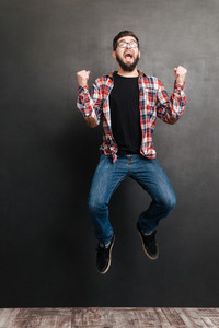 Excited man dressed in shirt in a cage and wearing glasses jumping over chalkboard while make winner gesture