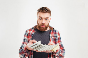 Excited young bearded man in plaid shirt looking at money banknotes with eyes wide open isolated on a white background