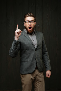 Excited young man in casual suit and glasses pointing up and having an idea isolated on the black wooden background