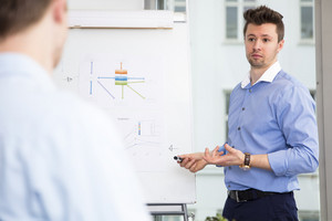 Executive Explaining Presentation To Colleague In Office