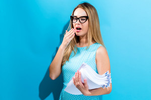 Exhausted office woman in glasses with a stack of documents