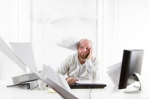 Exhausted office worker with documents flying around in the office. To much work.