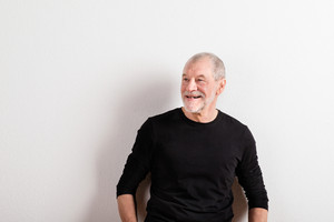 Face of handsome senior man in black sweater smiling. Studio shot against white wall.
