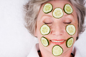 Face of mature woman with cucumber slices on it