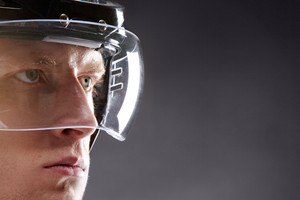 Face of sportsman in protective helmet looking seriously forwards