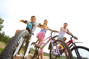 Family of three sitting on bikes, looking at camera and smiling