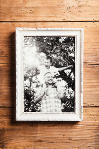 Family photo in white picture frame. Studio shot on wooden backgroung.