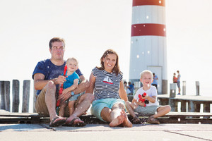 Family sitting on the pier at the lighthouse on sunny summer day