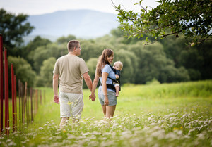 Family walking in the field with baby in the baby carrier
