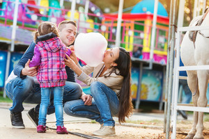 Family with daughter, amusement park, mother eating cotton candy, fun fair