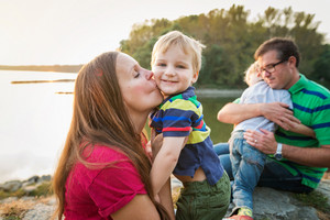 Family with two boys at the lake, sunny spring day. Parents hugging and kissing their children.
