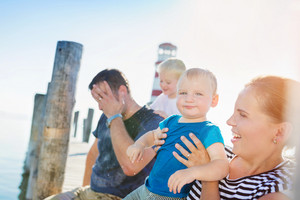 Family with two sons sitting on the pier at the lighthouse on sunny summer day