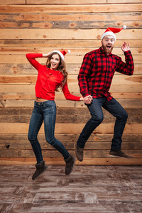 Fashion friends in santa's hats. full length portrait. Jumping. wooden background