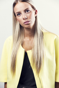Fashion portrait of a blonde woman in yellow jacket
