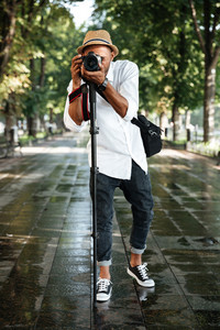 Fashionable black man in park with hat and camera