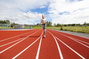 Fast athletic female runner on outdoor running track