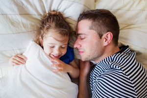 Father and daughter lying in parents bed, sleeping and smiling