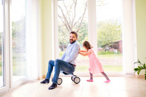 Father and daughter playing together, riding a bike indoors, sunny day