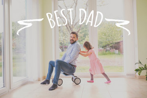 Father and daughter playing together, riding bike indoors. Fathers day concept.