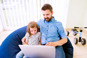 Father and daughter together, playing on laptop, sitting on bean bag, high angle view