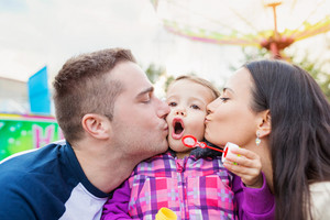Father and mother kissing their daughter blowing bubbles, family in amusement park, fun fair