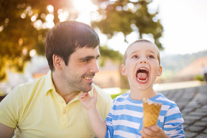 Father and son enjoying ice cream outside in a park