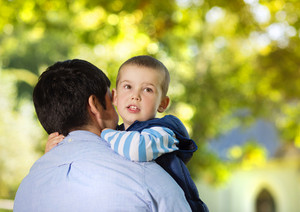 Father and son spending time together in sunny nature, son is hugging father