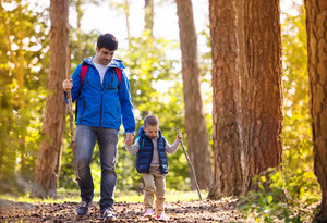 Father and son walking during the hiking activities in autumn forest at sunset