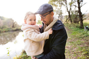 Father holding her little daughter in his arms. Walk by the lake, colorful autumn nature.