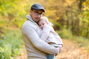 Father holding his little daughter in his arms. Walk in colorful autumn forest.