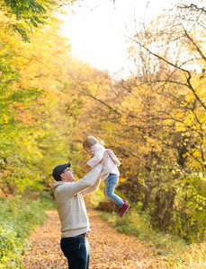 Father holding his little daughter, throwing her in the air. Walk in colorful autumn forest.