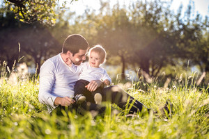 Father holding his little son, sitting on the grass in sunny nature