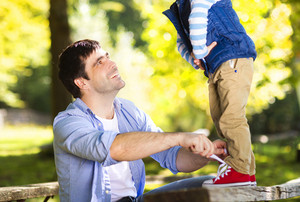 Father is helping his son to tie his shoes in summer nature