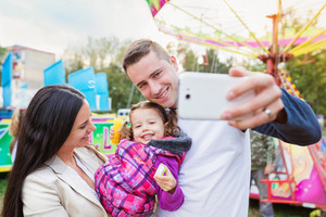 Father, mother and daughter in amusement park taking selfie, family at fun fair
