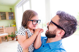 Father with his little daughter in black hipster eyeglasses, sunny day indoors