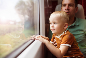Father with son in his lap traveling in train.