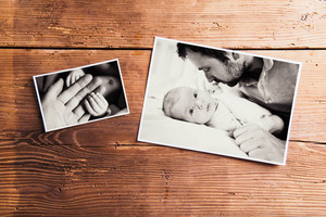 Fathers day composition. Black-and-white family pictures. Studio shot on wooden background.