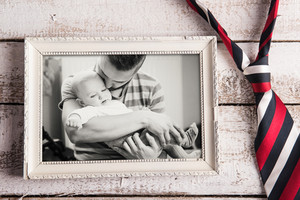 Fathers day composition. Black and white picture of father and daugter in picture frame, colorful tie. Wooden background. Studio shot on wooden background.