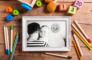 Fathers day composition. Black and white picture of father holding his daugter in picture frame and toys on the floor. Studio shot on wooden background.