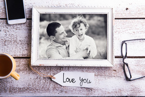 Fathers day composition. Black and white picture of father holding his son in picture frame. Studio shot on white wooden background.