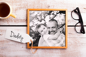 Fathers day composition. Black and white picture of father holding his son. Studio shot on white wooden background.