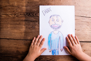 Fathers day composition. Hands of unrecognizable child holding a drawing of her father. Copy space. Studio shot on wooden background.