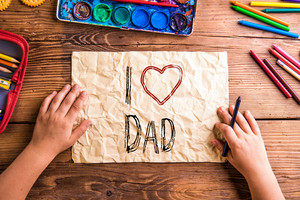 Fathers day composition. Hands of unrecognizable child with picture for her father with I love dad sign. Studio shot on wooden background.