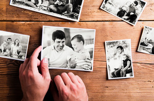 Fathers day composition. Hands of unrecognizable man holding  black-and-white photo. Studio shot on wooden background.