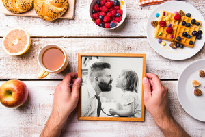 Fathers day composition. Hands of unrecognizable man holding black and white picture of him and his daughter in picture frame. Breakfast meal. Studio shot on white wooden background.