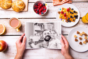 Fathers day composition. Hands of unrecognizable man holding black and white picture of him and his daughter taking selfie. Breakfast meal. Studio shot on white wooden background.