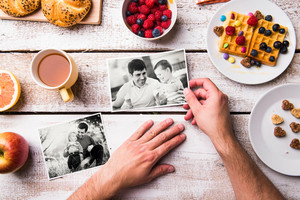 Fathers day composition. Hands of unrecognizable man holding black and white pictures of him and his sons. Breakfast meal. Studio shot on white wooden background.