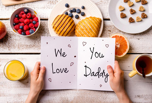 Fathers day composition. Hands of unrecognizable man holding greeting card with We love you, Daddy, text. Breakfast meal. Studio shot on wooden background.