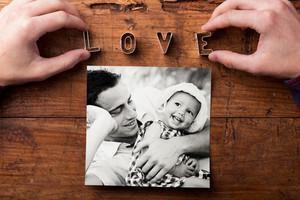 Fathers day composition. Hands of unrecognizable man, love sign made of cookie cutters, black-and-white family picture. Studio shot on wooden background.